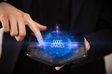 Young man holding a foldable smartphone with GOOD GRADES inscription, educational concept Banco de Imagens