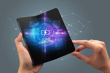 Businessman holding a foldable smartphone with TECHNOLOGY inscription, new technology concept CLOUD COMPUTING Banco de Imagens