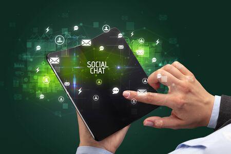 Businessman holding a foldable smartphone with SOCIAL CHAT inscription, social networking concept Banco de Imagens