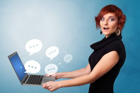 Woman holding laptop with a few speech bubble symbols