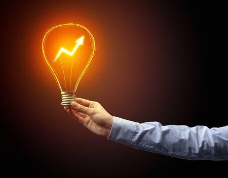 Hand holding light bulb on dark background. New Eco idea concept