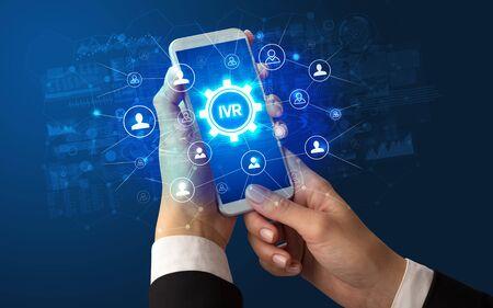 Weibliche Hand, die Smartphone mit IVR-Abkürzung hält, modernes Technologiekonzept