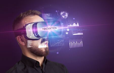 Businessman looking through Virtual Reality glasses with INNOVATION inscription, new business concept Stok Fotoğraf