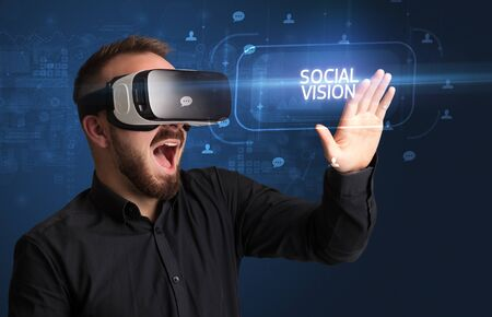 Businessman looking through Virtual Reality glasses with SOCIAL VISION inscription, social networking concept