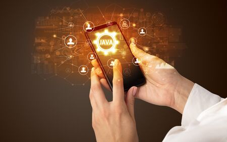 Female hand holding smartphone with JAVA abbreviation, modern technology concept