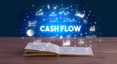 CASH FLOW inscription coming out from an open book, business concept