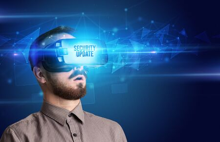 Businessman looking through Virtual Reality glasses with SECURITY UPDATE inscription, cyber security concept