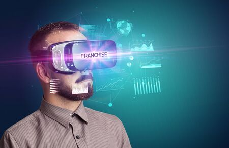 Businessman looking through Virtual Reality glasses with FRANCHISE inscription, new business concept