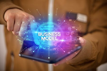 Businessman holding a foldable smartphone with BUSINESS MODEL inscription, new business concept Фото со стока - 133388516