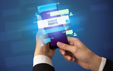Female hand typing on smartphone with HUMAN RIGHTS inscription, social networking concept