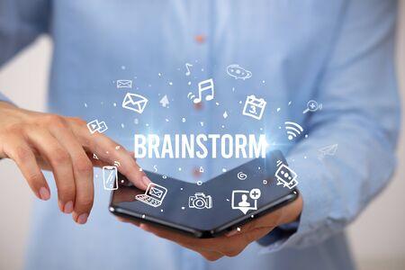 Businessman holding a foldable smartphone with BRAINSTORM inscription, social media concept