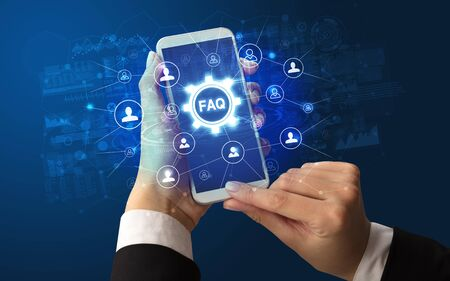 Female hand holding smartphone with FAQ abbreviation, modern technology concept Фото со стока