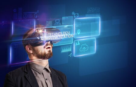 Businessman looking through Virtual Reality glasses with TECHNOLOGY IMPLEMENTATION inscription, new technology concept