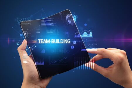 Businessman holding a foldable smartphone with TEAM BUILDING inscription, successful business concept Stock fotó