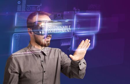 Businessman looking through Virtual Reality glasses with SUSTAINABLE DEVELOPMENT inscription, new technology concept