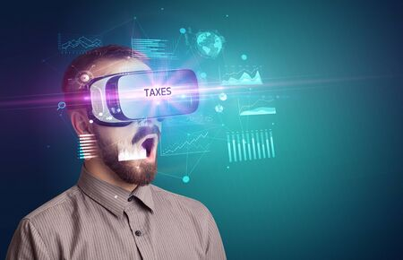 Businessman looking through Virtual Reality glasses with TAXES inscription, new business concept