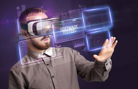 Businessman looking through Virtual Reality glasses with SOFTWARE TESTING inscription, new technology concept