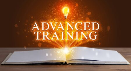 ADVANCED TRAINING inscription coming out from an open book, educational concept Stock fotó