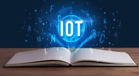 IOT inscription coming out from an open book, digital technology concept Stock fotó - 133388619