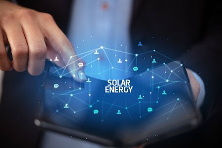 Businessman holding a foldable smartphone with SOLAR ENERGY inscription, new technology concept