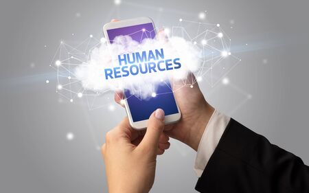 Female hand touching smartphone with HUMAN RESOURCES inscription, cloud business concept Фото со стока