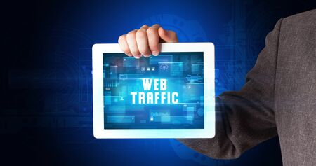 Young business person working on tablet and shows the digital sign: WEB TRAFFIC Stock fotó - 133388652