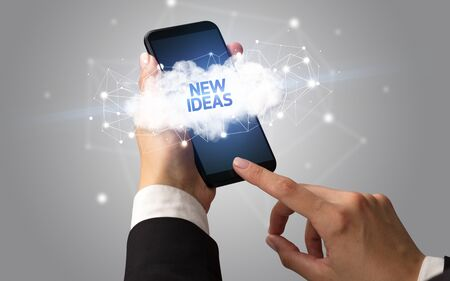 Female hand touching smartphone with NEW IDEAS inscription, cloud business concept Фото со стока