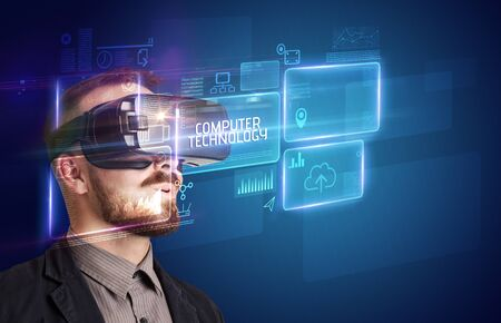 Businessman looking through Virtual Reality glasses with COMPUTER TECHNOLOGY inscription, new technology concept