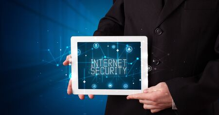Young business person working on tablet and shows the digital sign: INTERNET SECURITY