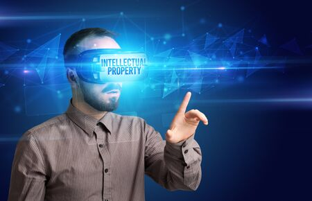 Businessman looking through Virtual Reality glasses with INTELLECTUAL PROPERTY inscription, cyber security concept