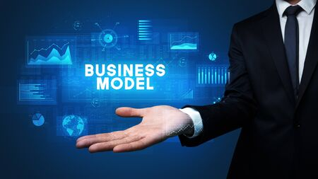 Hand of Businessman holding BUSINESS MODEL inscription, business success concept