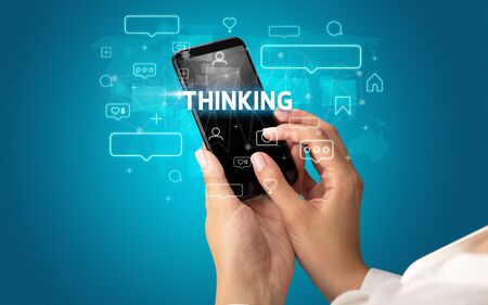 Female hand typing on smartphone with THINKING inscription, social media concept