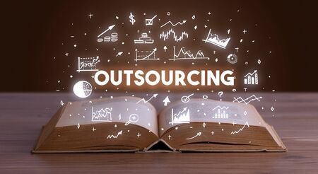 OUTSOURCING inscription coming out from an open book, business concept