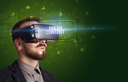 Businessman looking through Virtual Reality glasses with FRESH CONTENT inscription, social networking concept