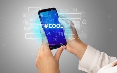 Female hand typing on smartphone with #COOL inscription, social media concept