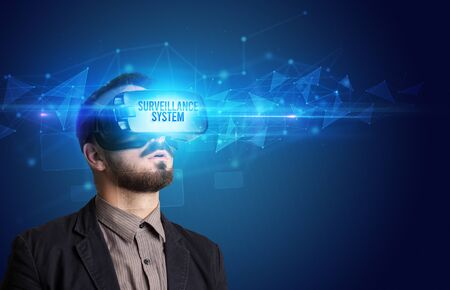 Businessman looking through Virtual Reality glasses with SURVEILLANCE SYSTEM inscription, cyber security concept Stock fotó - 133388696