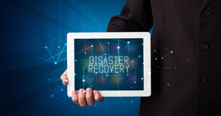 Young business person working on tablet and shows the digital sign: DISASTER RECOVERY Stock fotó - 133388695