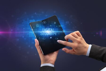 Businessman holding a foldable smartphone with DIGITAL SECURITY inscription, cyber security concept