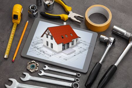 Tablet with construction tools and 3d home plan concept 写真素材