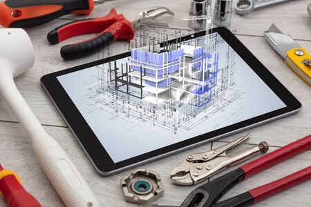 Tablet with construction tools and 3d house plan concept 写真素材