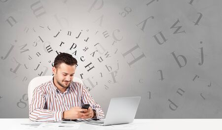 Business person sitting at desk with editorial and letters concept Reklamní fotografie - 133554468