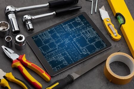 Tablet with construction tools and blueprint concept