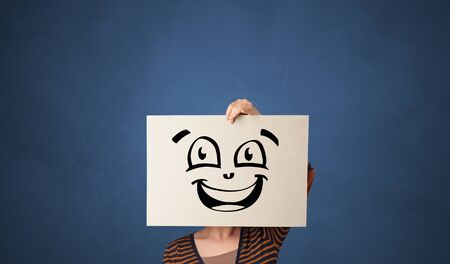 Casual person holding a paper in front of his face with drawn emoticon face Фото со стока