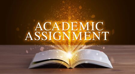 ACADEMIC ASSIGNMENT inscription coming out from an open book, educational concept 写真素材