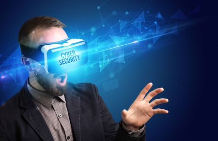 Businessman looking through Virtual Reality glasses with CYBER SECURITY inscription, cyber security concept Stock Photo