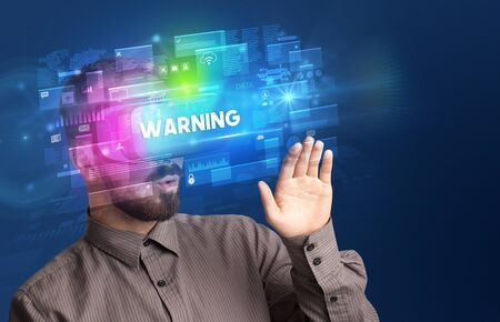 Businessman looking through Virtual Reality glasses with WARNING inscription, innovative security concept