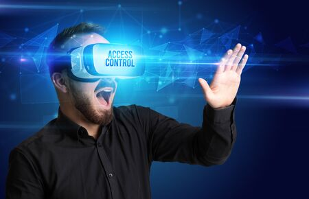 Businessman looking through Virtual Reality glasses with ACCESS CONTROL inscription, cyber security concept