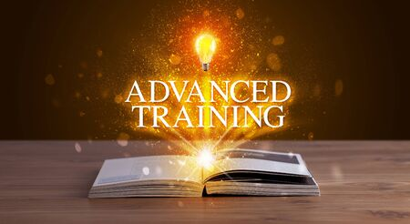 ADVANCED TRAINING inscription coming out from an open book, educational concept 写真素材