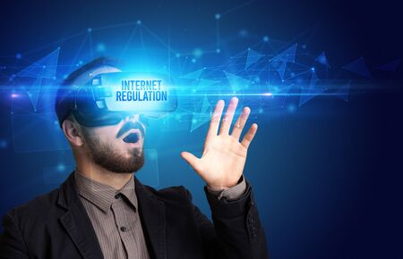Businessman looking through Virtual Reality glasses with INTERNET REGULATION inscription, cyber security concept Stock Photo