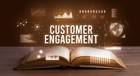 CUSTOMER ENGAGEMENT inscription coming out from an open book, creative business concept 写真素材